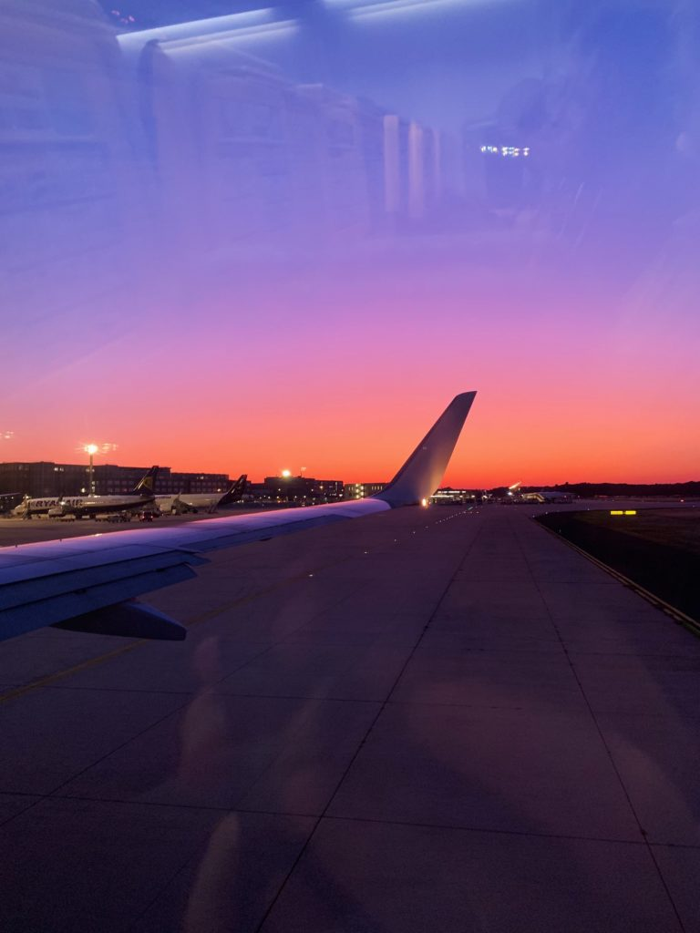 View of the airplane wing at sunrise from the inside of the plane.
