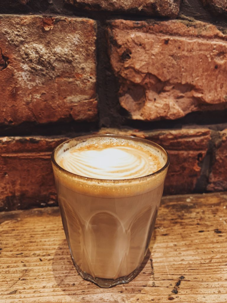 double shot latte in a small glass in front of a red brick wall