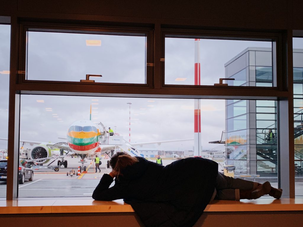 A woman is laying on her side on a ledge looking out a window at an airplane being prepped in an airport.