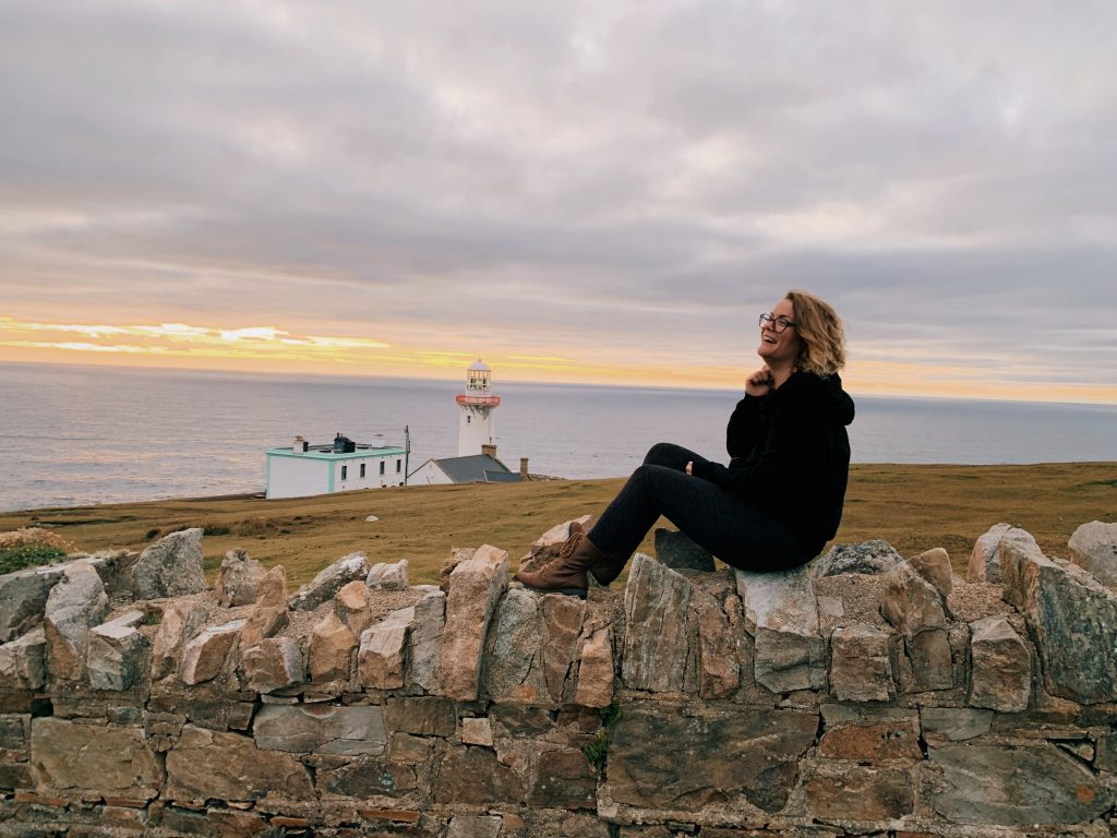 Coco sitting and laughing atop a rock wall at sunset with a lighthouse and the atlantic ocean behind her.