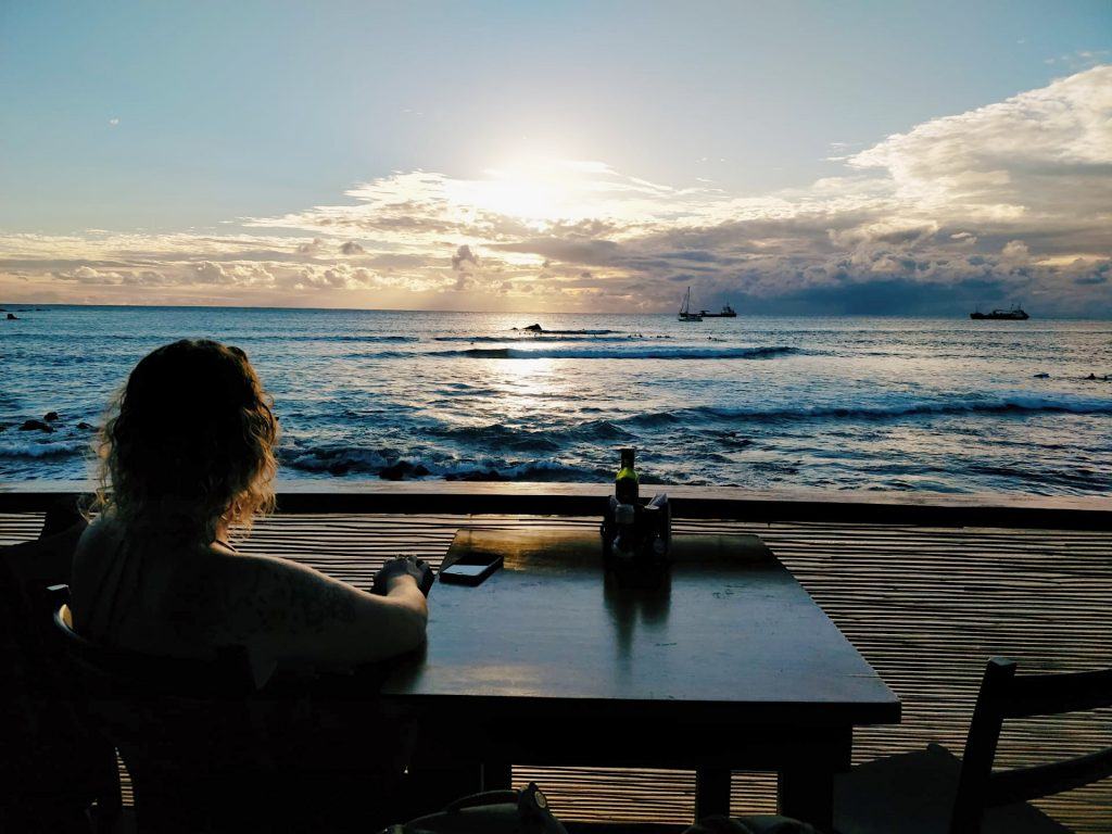 Coco sitting at a table overlooking the ocean as the sun is setting behind scattered clouds and boats dot along the horizon.