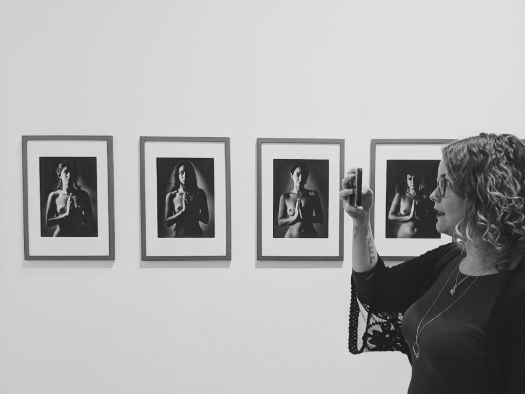 Coco Standing take a photo to the left while in front of 4 separate black and white photographs of women looking straight towards the camera without any clothes on.