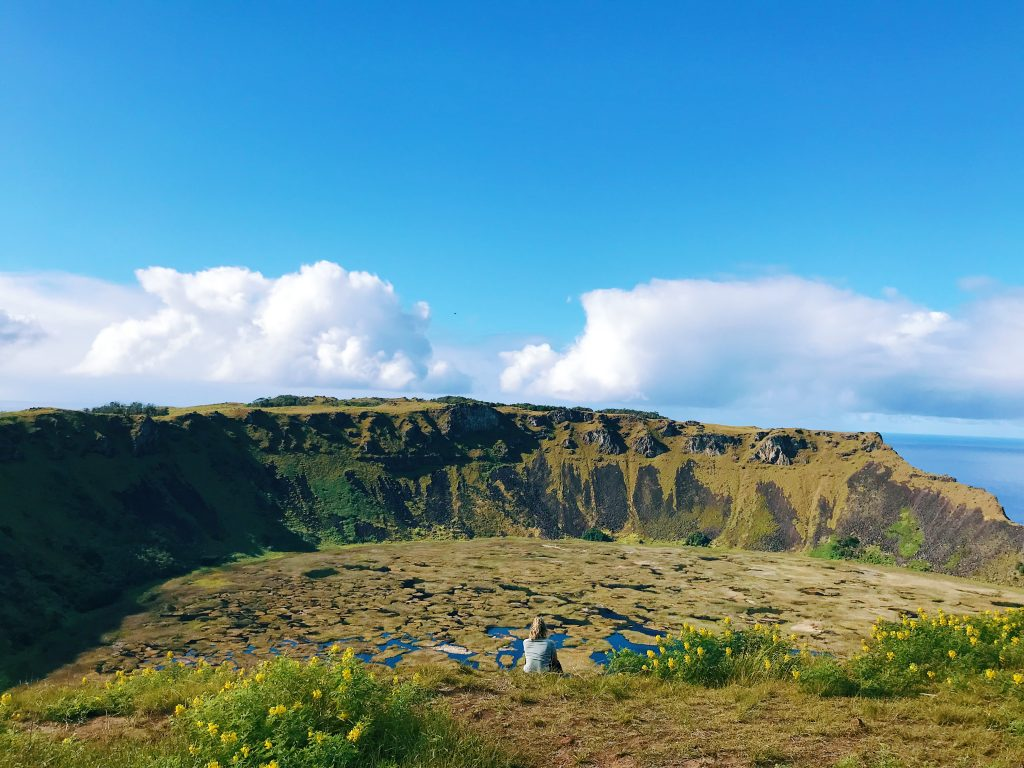 Courtney sitting at the edge of a Volcano Crater on Rapa Nui, Easter Island - taking a moment to breathe.
